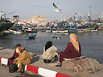 Women sit on the dockside waiting for fishing boats to return, Essouira, Morocco