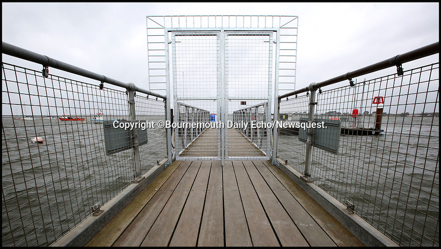 """BNPS.co.uk (01202 558833)<br /> Pic: Corin Messer/BNPS<br /> <br /> An 'Alcatraz' style steel gate has ruffled the normally genteel feathers of the well heeled beach hut residents of Mudeford in Dorset.<br /> <br /> The views from Britain's most expensive beach huts have been blighted by a set of """"prison style"""" gates officials have put up on a ferry jetty because they feared it was becoming dangerous.<br /> <br /> The owners of the exclusive huts that change hands for an eye-watering £250,000 are outraged after the 8ft stainless steel gates appeared on the end of the jetty.<br /> <br /> Health and safety officials put up the lockable gates amid fears unauthorised boats using the wooden pontoon at Mudeford Spit, Dorset, <br /> were posing a risk to the small ferry service that uses it."""