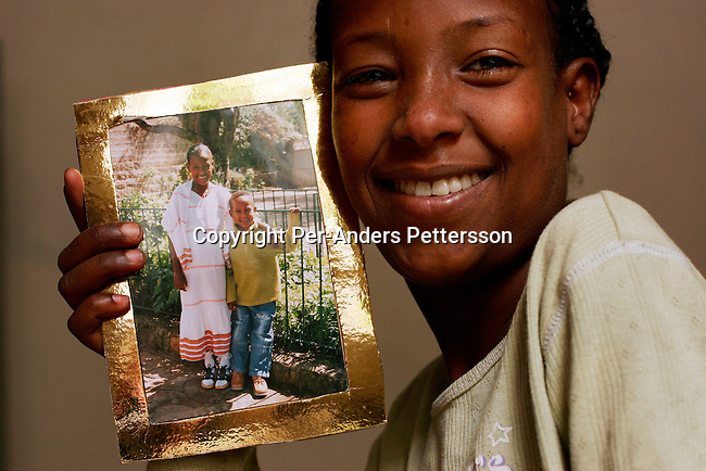 ADDIS ABABA, ETHIOPIA APRIL 7:  Amelezewd Gahw, age 11, shows a photo of herself and her brother. She lost both her parents to HIV-Aids. Amalezewd was with her mother when she died.  She stays at Ahope orphanage in Addis Ababa, Ethiopia, on April 7, 2005. The orphanage houses about 40 children, some of them infected by HIV-Aids..(Photo by Per-Anders Pettersson/Getty Images)..
