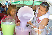 Hmong outdoor restaurant worker filling tub with purple juice. Hmong Sports Festival McMurray Field St Paul Minnesota USA