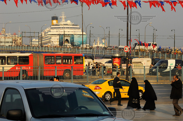 Muslim women shrouded in black in Eminonu with traffic, the Galata Bridge, and a giant cruise liner docked behind.