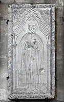 Tombstone of Hugues Libergier, 1229-63, architect of the Church of Saint-Nicaise at Reims, now destroyed, in the Cathedrale Notre-Dame de Reims or Reims Cathedral, Reims, Champagne-Ardenne, France. His engraved effigy has him in 13th century costume with a model of the Saint-Nicaise church in his right hand, from where the tombstone was moved. The cathedral was built 1211-75 in French Gothic style with work continuing into the 14th century, and was listed as a UNESCO World Heritage Site in 1991. Picture by Manuel Cohen