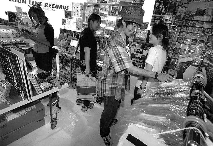 "8/10/2002--Shimokitazawa, Tokyo, Japan..high Line Records, one of many independent music labels in Shimo that also sells clothing and other cool accessories..Executives from the big music companies are frequently spotted cruising the local clubs and music stores for fresh talent. High Line, which stocks what may be the largest selection of Japanese indie music in the country, gets into the act, too. Two years ago, the shop launched a record company to give aspiring bands a boost. One of High Line's discoveries, folk-rock band Bump of Chicken, recently signed a contract with mainstream label Toy's Factory...Wedged between Tokyo's Shinjuku and Shibuya wards, Shimokitazawa's maze of narrow streets form the ramparts of all that is non-conformist in get-along, go-along Japan. In ""Shimokita,"" old village shops trade happily beside newer, eccentric clothing stores, funky restaurants, matchbox playhouses and live-music clubs. The unpretentious ambience is a magnet for students and other young visitors for whom Tokyo's usual street fashion scene has become more fascist than fun and mainstream entertainment is, well, too mainstream. Musicians, designers, aspiring actors and other would-be iconoclasts have settled the area, as have young professionals opting for a less-structured lifestyle. ...All photographs ©2003 Stuart Isett.All rights reserved.This image may not be reproduced without expressed written permission from Stuart Isett."