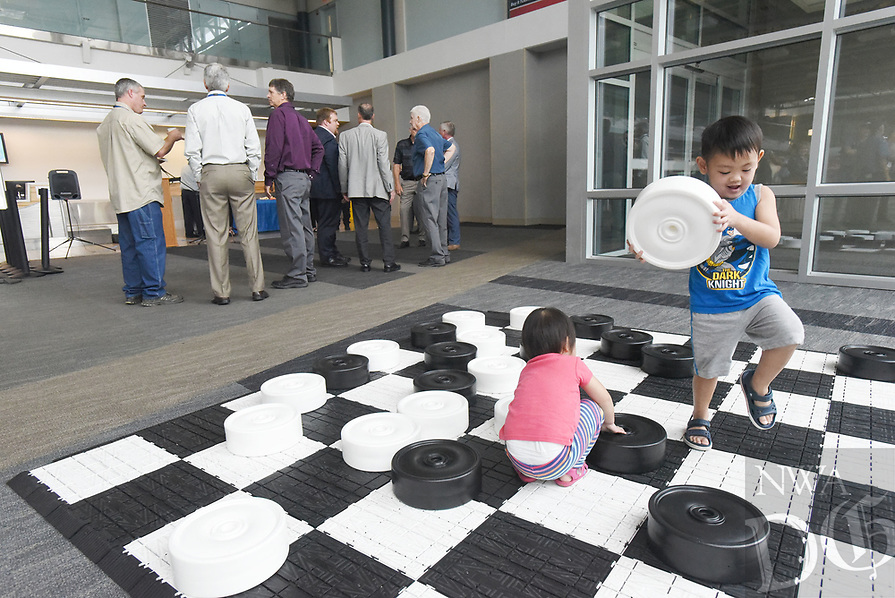 NWA Democrat-Gazette/FLIP PUTTHOFF <br /> Children play with a jumbo checkers game Tuesday Aug. 13 2019 as guests gather for the announcement of more flights from Northwest Arkansas Regional Airport.