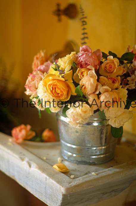 Garden roses are arranged in a small aluminium bucket