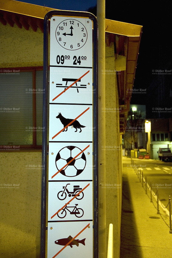 Italy. Lombardy region. Campione d'Italia. Night scene. A sign forbids various activities during day and evening time: picnic, dogs, play ball, run a bike, a lightweight motor cycle or a motorbike, fish. Campione d'Italia is occupying an enclave within the Swiss canton of Ticino, separated from the rest of Italy. 28.02.2008© 2008 Didier Ruef .