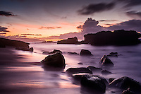 Colorful sunset reflecting off a rocky shoreline, North Shore, Oahu, Hawaii