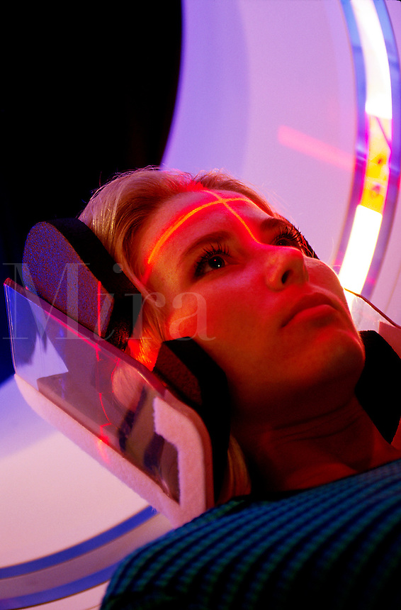 Female patient undergoes a CAT scan. Close up of interior illumination of device and head and face of patient.