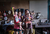 51 year old Goh Kuam Boon, a former pig farmer and a  survivor of the Nipah virus poses for a portrait with his wife and his grandchildren in the kitchen of their house in Bukit Pelandok in Nageri Sembilan, Malaysia on October 16th, 2016. <br /> In September 1998, a virus among pig farmers (associated with a high mortality rate) was first reported in the state of Perak in Malaysia. Dr. Chua investigated and discovered the virus and it was later named, Nipah Virus. The outbreak in Malaysia was controlled through the culling of &gt;1 million pigs.