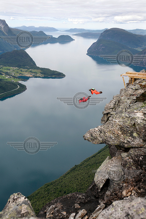 JT Holmes (left, USA)  race Andrey Kar (Russia) race during World Base Race, the first event where BASE jumpers compete to be the fastest flying down from a mountain, before deploying their parachute. The the contestants jump from a mountain in the fjord Innfjorden in Western Norway, two jumpers race each other to the finish line 750 meters horizontally from the mountain.