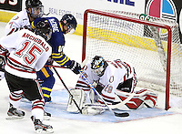 Nebraska Omaha's Josh Archibald and Michael Young hold back University of British Columbia's Justin McCrae as goalie Dayn Belfour freezes the puck. (Photo by Michelle Bishop)