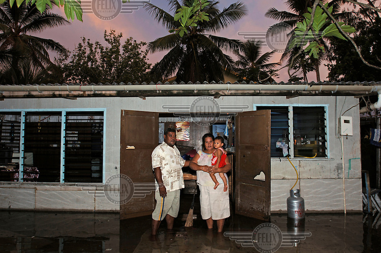 Elesia and Fialua and their children stand outside their home, from which they were evacuated with the arrival of floodwaters.  The coral atoll is to vulnerable to sea level rise, particularly at high spring tides, when water seeps up through the ground and causes flooding..