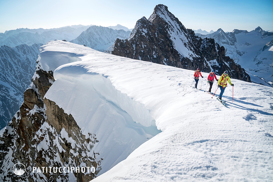 Ski touring on a corniced ridge of the Ränfenhorn before making the huge descent of the Rosenlaui Glacier on the last day of the Berner Haute Route, Switzerland
