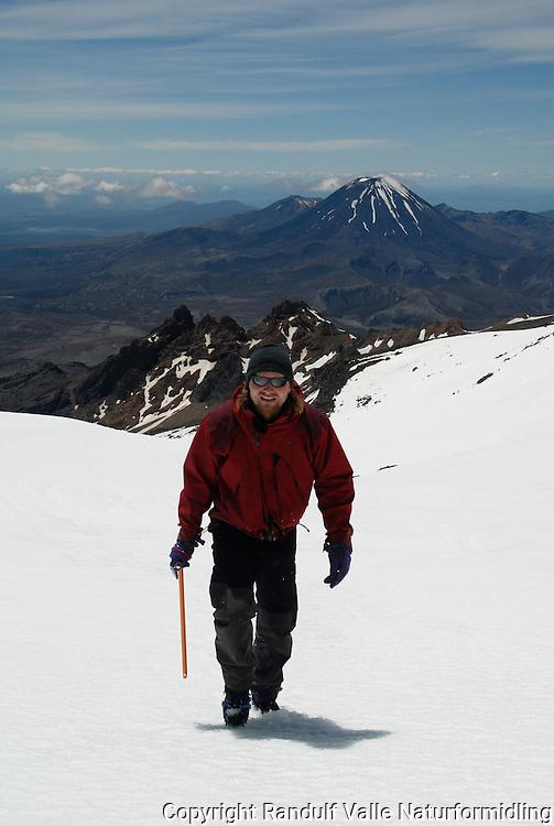 Mann på vei opp Mt Ruapehu. Mt Ngauruhoe i bakgrunnen ---- Man climbing the slopes ov Mt Ruapehu. Mt Ngauruhoe in the background