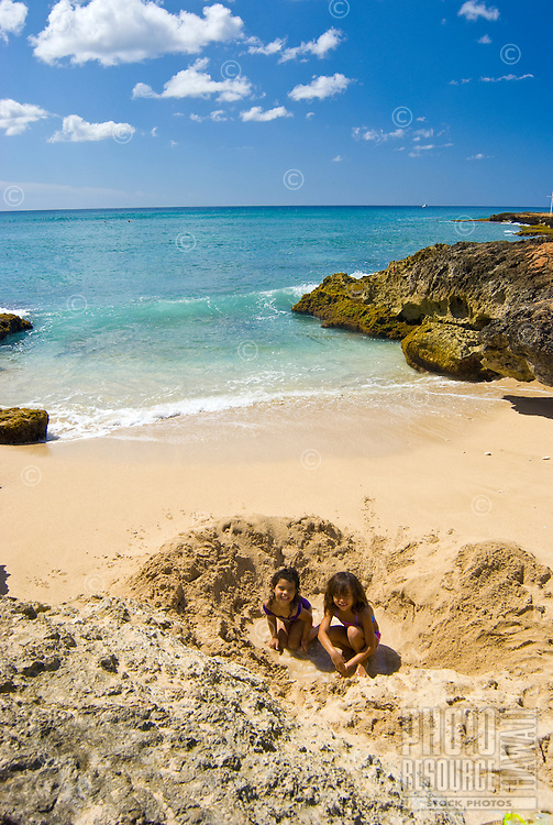 Two girls playing in the sand at the beach at Makaha