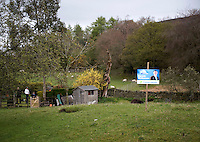 A Conservative Party election campaign poster stands in a garden in the Lake District. Parliamentary candidate Gareth McKeever encourages people to vote for his party under the slogan Vote For Change.