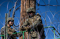 "MEXICALI,  MEXICO - November 26. US army soldiers are seen from the mexican side fortifying US-Mexico border wall with barbed wire on November 26, 2018 in Mexicali, Mexico.<br /> The U.S. government said it was starting work to ""harden"" the border crossing  Mexico, to prepare for the arrival of a migrant caravan leapfrogging its way across western Mexico. For the Trump administration and those who support the president's hard-line stance on illegal immigration, the chaos illustrated what they long have feared. For others, the images of the Border Patrol using tear gas on a group of migrants that included children were deeply disturbing (Photo by Luis Boza/VIEWpress)"