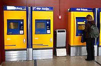 Vrouw koopt treinkaartje uit een automaat