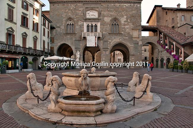 The fountain in the Piazza Vecchia in Bergamo, Italy with the Palazzo della Ragione and the Colleoni Chapel in the background