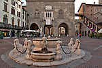 The fountain in the Piazza Vecchia in Bergamo, Italy with the Palazzo della Ragione and the Colleoni Chapel in the background
