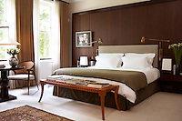 A wood-panelled bedroom is furnished with a comfortable double bed and a wooden bench for books