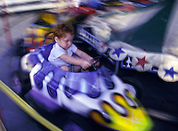 Blurred motion image of a young boy on an amusement park ride.