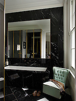 The master bath is sheathed in Nero Marquina marble, the 1950s slipper chair is by Ico Parisi and the 1950s vase by Ercole Barovier was a Paris flea-market find.