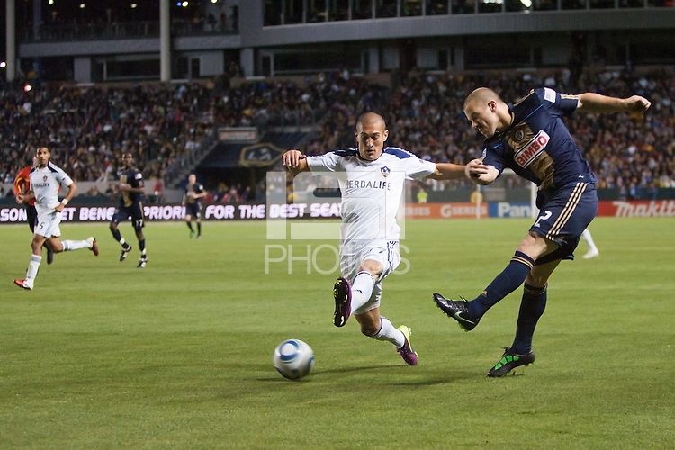 Jordan Harvey (2) of the Philadelphia Union sends a ball past LA Galaxy midfielder Bryan Jordan (27). The LA Galaxy defeated the Philadelphia Union 1-0 at Home Depot Center stadium in Carson, California on  April  2, 2011....