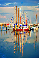 Sailboats reflected in the quiet waters of the San Sebastian River at sunset on a spring evening. Located in beautiful St. Augustine, Florida