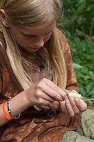 Holunderkette, Holunder-Kette, Mädchen, Kind bastelt eine Kette aus Holunder, das Mark wird mit einem Stöckchen herausgedrückt, Holunderzweig, Indianerkette, Bastelei, Naturbastelei, Schmuck aus Naturmaterialien, Naturschmuck, Holundermark
