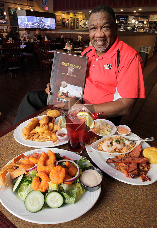 The Gulf Shores Restaurant & Grill in Edwardsville is the second location of the popular Cajun-themed eatery which has another site in St. Louis. This location is within the Edwardsville Crossing shopping complex. Owner Harry Parker holds a menu at a table loaded with favorites from his restaurant. Clockwise from front left is the Buffalo Shrimp Salad (Romaine and field greens, tossed with grape tomatoes, cucumbers, red onions, and cheese and topped with jumbo battered shrimp coated with Frank's Red Hot Sauce and other Cajun seasonings, and served with homemade Cajun Ranch dressing); the Seaside Combo (two hand-battered Cod fish fillets and six jumbo shrimp); and the Bourbon Street Combo (homemade jambalaya, Andouille sausage, homemade crab cake and red beans with rice). The drink at center is a Pat O'Brien Hurricane (named after the classic drink that originated at the famous New Orleans bar).