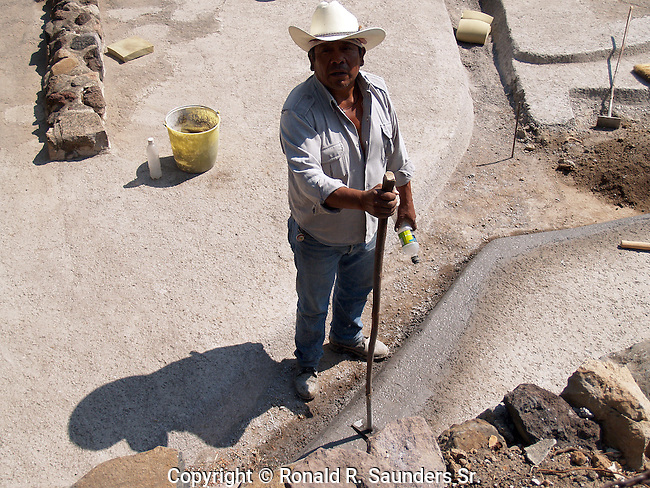 CEMENT WORKER FIXES RAIN DRAIN AT PYRAMIDS IN MEXICO DF