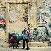 Old Colombian men drink a no-name Caribbean rum while sitting on the street bellow a large mural in Getsemaní, a popular artistic neighborhood in Cartagena, Colombia, 16 April 2018.