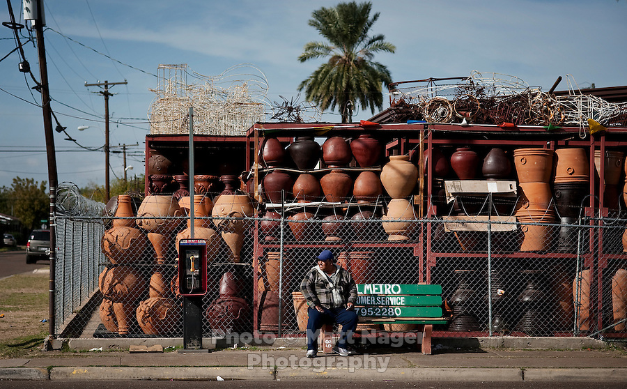 A man waits for a bus in front of  Mexican Import store in West Laredo, Texas, Tuesday, Dec., 8, 2009. ..PHOTOS/ MATT NAGER