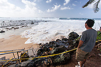 A spectator watches waves approaching public beach access stairs during the giant swell of January 22, 2014, at Keiki Beach, North Shore, O'ahu.