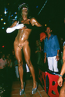 Spain. Ibiza in the Balearic islands. Ibiza. Night life. Amnesia Disco. A sexy young man dances on the sound of the techno music. He is fully naked with just a mirror to hide his penis. He wears a queen's crown on his headand, high-heeled shoes, a white glove on the right arm and hand, a black glove on the left arm and hand. Transsexualism is a condition in which an individual identifies with a physical sex that is different from their biological one. © 1999 Didier Ruef