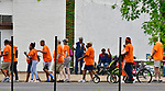 The Wear Orange Day March against gun violence passes by a sidewalk sale outside the Temple of God Missionary Baptist Church on Saturday June 2, 2018. The walk began at St. Alphonsus Liguori Catholic Church and proceeded north on North Grand Boulevard to the Herbert Hoover Boys & Girls Club where a rally and resource fair was held. June is National Gun Violence Awareness Month.<br /> Photo by Tim Vizer