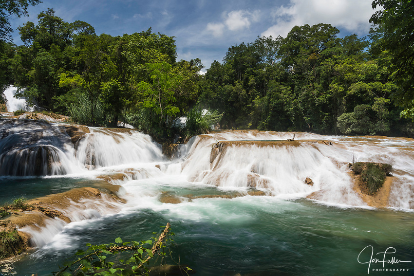 The Agua Azul Waterfalls are a series of cascades on the Xanil River in Chiapas, Mexico.  The river is a turquoise color because of the high mineral content in the water.