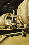 Still life of bottle of whisky and glasses in atmospheric bonded warehouse at Bladnoch Distillery near Wigtown in the Machars of Galloway Scotland UK