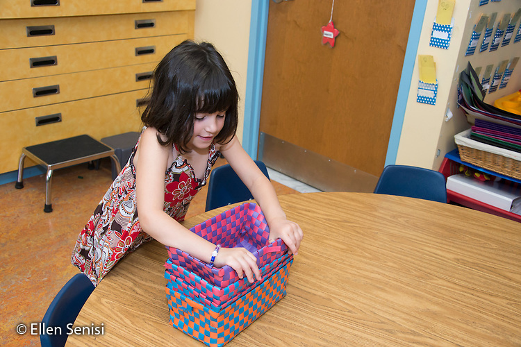 MR / Schenectady, NY. Zoller Elementary School (urban public school). Kindergarten classroom. Student (girl, 5) fits nesting baskets inside each other. MR: Coh2. ID: AM-gKw. © Ellen B. Senisi.