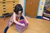 MR / Schenectady, NY. Zoller Elementary School (urban public school). Kindergarten classroom. Student (girl, 5) fits nesting baskets inside each other. MR: Coh2. ID: AM-gKw. © Ellen B. Senisi.