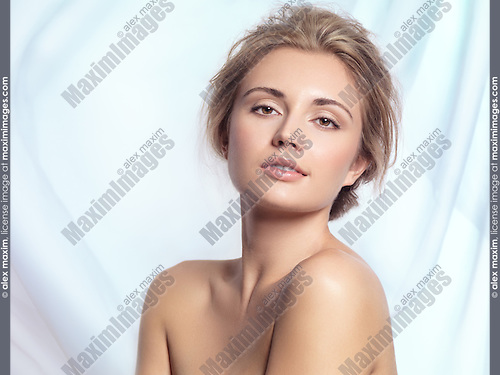 Beauty portrait of a young woman with natural clean makeup and contemporary hairstyle over light blue flowy fabric background