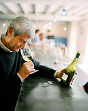 FRANCE, Chablis, Burgundy, the owner Michael Laroche smelling wine at the bar, Laroche Restaurant