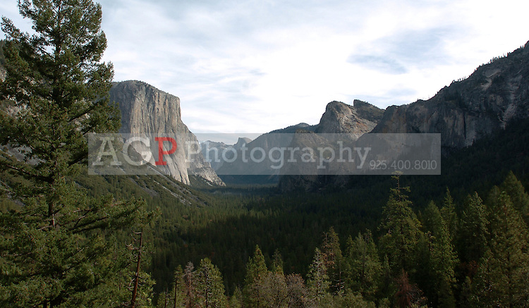 """El Capitan, left, Half Dome, center, and Bridalveil Falls are seen in this view from near the tunnel on WInona Highway in one of the most famous views of Yosemite Valley in California on November 24, 2008. Yosemite's Tunnel View Overlook, located next to Wawona Road at the east portal of the Wawona Tunnel, was constructed during an era that heralded a boom in design and development throughout the National Park Service, and helped initiate the service's """"rustic"""" design style. Because of their exemplary park service rustic design, Wawona Tunnel and Tunnel View are listed on the National Register of Historic Places. The site remains one of the most popular scenic overlooks in Yosemite National Park. Tour buses, tram tours, and single-family vehicles bring as many as 7,000 people to the site each day during the height of the visitor season. (Photo copyright Alan Greth)"""