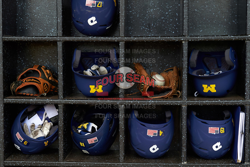 Michigan Wolverines helmets, gloves, and baseballs in the helmet rack before the first game of a doubleheader against the Canisius College Golden Griffins on June 20, 2016 at Tradition Field in St. Lucie, Florida.  Michigan defeated Canisius 6-2.  (Mike Janes/Four Seam Images)