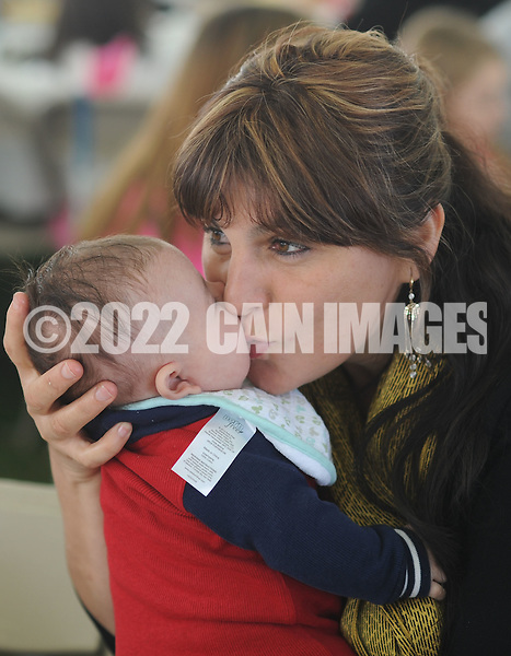 Maria Rodriguez (right) of Levittown, Pennsylvania kisses Matthew Landavermy, 3 moths old, on the cheek during the combined parishes Octoberfest Sunday October 18, 2015 at Queen of the Universe Church in Levittown, Pennsylvania.  Immaculate Conception Church in Bristol closed and merged with Queen of the Universe Church last year. (Photo by William Thomas Cain)