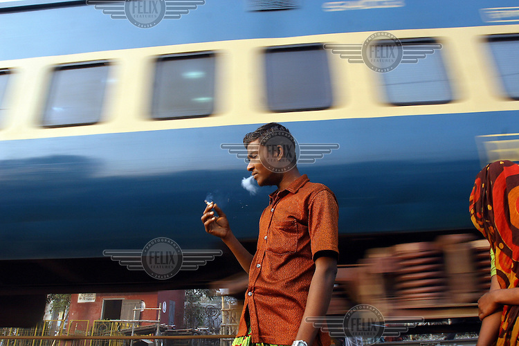 A man, living in a slum, smokes a cigarette as a commuter train rushes past. Many slums have grown up along railway tracks and accidents involving slum dwellers are common.