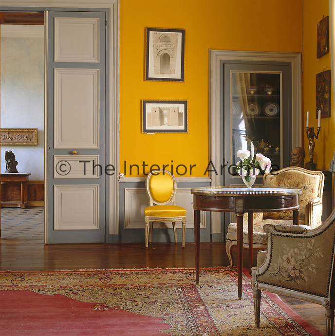 A corner of the yellow-painted Grand Salon which opens off one side of the dramatic entrance hall