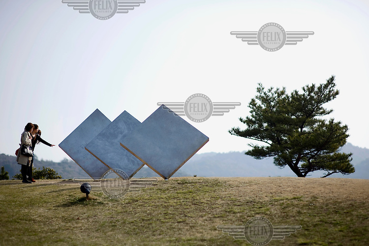 A woman reaches out to touch an installation, depicting a ship on the beach, at the Benesse Art House on Naoshima Island. /Felix Features