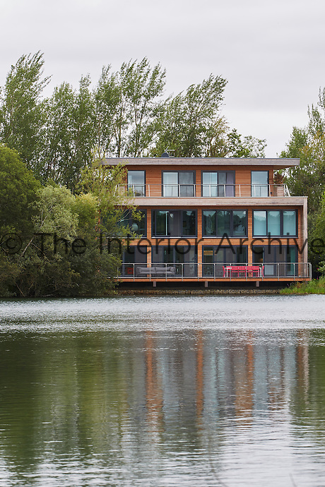 A stunning, three storey riverside house with floor to ceiling windows and a large deck, which runs the entire width of the house too for outdoor eating and seating and access to paddle boards and canoes.
